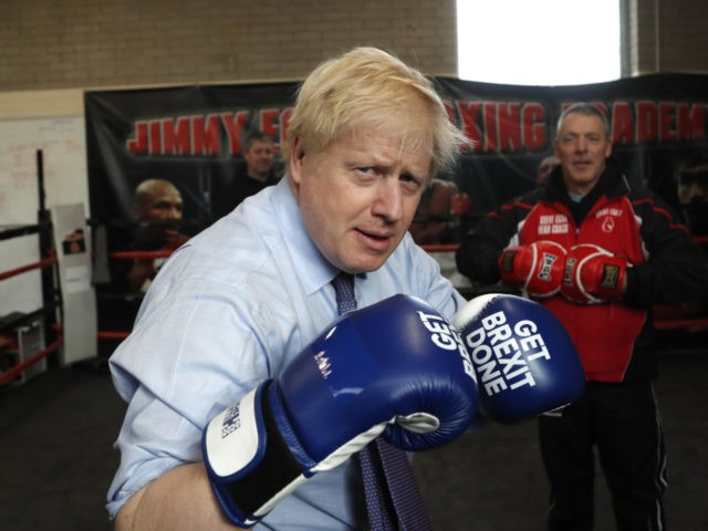 "MANCHESTER, ENGLAND - NOVEMBER 19: Britain's Prime Minister Boris Johnson poses for a photo wearing boxing gloves emblazoned with ""Get Brexit Done"" during a stop in his General Election Campaign trail at Jimmy Egan's Boxing Academy on November 19, 2019 in Manchester, England. Britain goes to the polls on Dec.12. …"