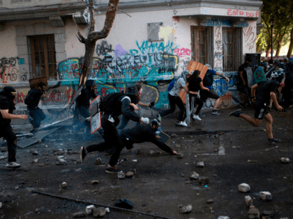 Demonstrators run to escape from riot police during a protest against the government in Santiago on November 19, 2019. - President Sebastian Pinera condemned on Sunday for the first time what he called abuses committed by police in dealing with four weeks of violent unrest that have rocked Chile and …