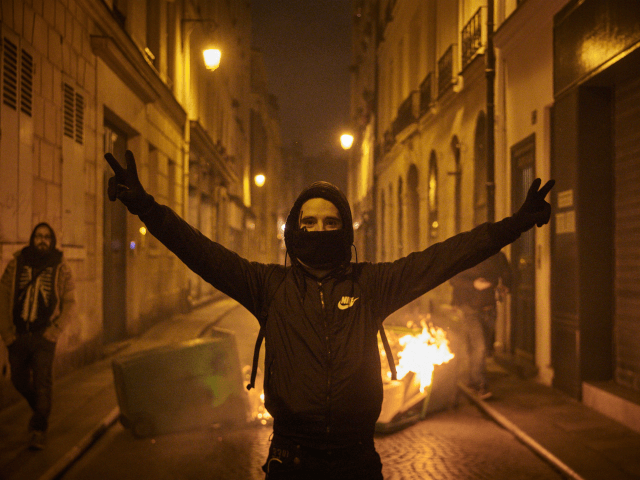 PARIS, FRANCE - NOVEMBER 16: A Black Bloc protestor celebrates next to a burning barricade as protests to mark the Anniversary of the Gilets Jaune movement turn violent in Paris as thousands of protesters converged on the French capital on November 16, 2019 in Paris, France. One of the most …