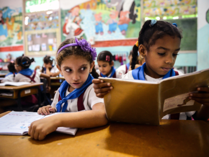 Cuban schoolgirls read during class, on November 13, 2012, in Havana. AFP PHOTO (Photo credit should read STR/AFP via Getty Images)