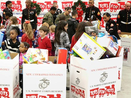 WASHINGTON, DC - DECEMBER 19: U.S. first lady Michelle Obama (L) helps children to sort gifts for the Marine Corps' Toys for Tots Campaign December 19, 2013 at Joint Base Anacostia-Bolling in Washington, DC. The first lady delivered toys and gifts donated to the campaign during the event and visited …