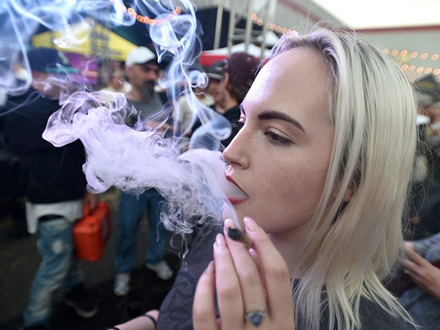 A woman from Seattle, smokes a joint at the first annual DOPE Cup, a cannabis competition in Portland, Oregon, on October 4, 2015. As of October 1, 2015 limited amounts of recreational marijuana became legal for all adults over the age of 21 to purchase in the state of Oregon. …