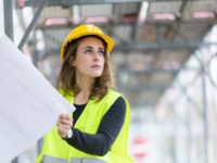 Female construction worker with helmet and safety jacket on construction site examining office blueprints. Outdoors