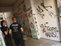 "BERLIN, GERMANY - JULY 12: Graffiti, including one scrawl that reads: ""Kill Cops and Nazis"", covers the entrance to the apartment building at Rigaer Strasse 94 as police stand by on July 12, 2016 in Berlin, Germany. Rigaer Strasse, and especially Rigaer Strasse 94 , have become the focus of …"
