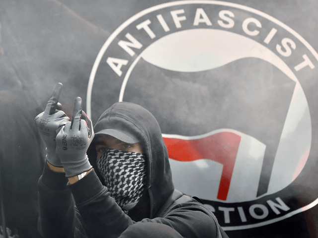 TOPSHOT - A demonstrator gestures in front of an Antifascist Action flag during a demonstration against the controversial labour reforms of the French government in Nantes, western France, on September 15, 2016. Opponents of France's controversial labour reforms took to the streets on September 15, 2016 for the 14th time …