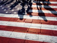 Shadows of group of people walking through the streets with painted Usa flag on the floor. Concept political relations with neighbors.