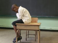 Boy sitting on top of desk by blackboard