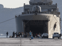 Migrants wait outside a military vessel after their disembarkation at the port of Elefsina, near Athens, on Saturday, Nov. 2, 2019. The transfer of migrants from overcrowded camps on the islands to the Greek mainland continued this weekend, with 415 arriving Saturday afternoon at the port of Elefsina west of …