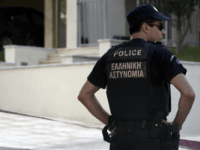 A police officer stands in front of the house of Greek journalist Socratis Guiolas, after the latter was killed, on July 19, 2010 in Athens. Gunmen shot and killed Guiolas, early Monday in front of his home near Athens, before fleeing in a car, police said. At least three unknown …