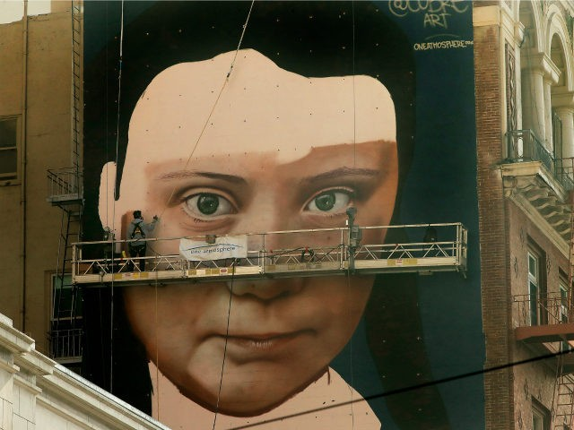 Andres Petreselli paints a mural on the side of a building depicting Swedish teen climate activist Greta Thunberg, Friday, Nov. 8, 2019, in San Francisco. (AP Photo/Ben Margot)