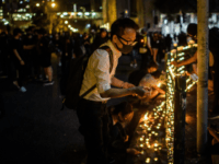 Mourners light candles on a street handrail as they pay their respects outside the carpark where 22-year-old student Alex Chow fell during a recent protest in the Tseung Kwan O district on the Kowloon side of Hong Kong early on November 9, 2019. - Thousands of Hong Kongers held vigils …