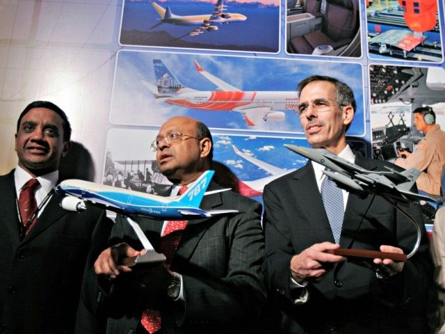 The Boeing Company Chief Technology Officer and Senior Vice President of Engineering, Operations and Technology John J. Tracy, right, and Boeing India President Dinesh A. Keskar, center, hold miniatures of the company's aircraft, as Boeing India Vice President Engineering and Technology Naveed Hussain looks on during the launch of the …