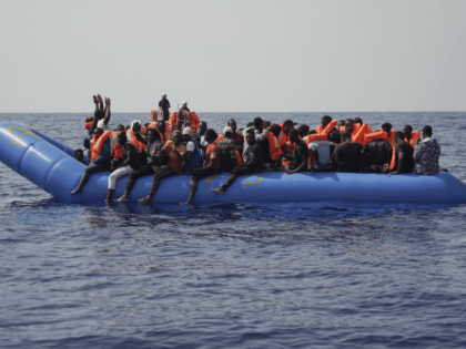 Men aboard a blue plastic boat point to the sky in the Mediterranean Sea, Tuesday, Sept. 17, 2019. The humanitarian rescue ship Ocean Viking saved 109 people from two unseaworthy boats. (AP Photo/Renata Brito)