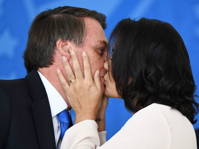 Brazilian President Jair Bolsonaro (L) and First Lady Michelle Bolsonaro kiss during the commemoration ceremony of the National Volunteer Day, at Planalto Palace in Brasilia, on August 28, 2019. - Bolsonaro on Wednesday repeated a demand for French leader Emmanuel Macron to withdraw recent remarks, as he accused France and …
