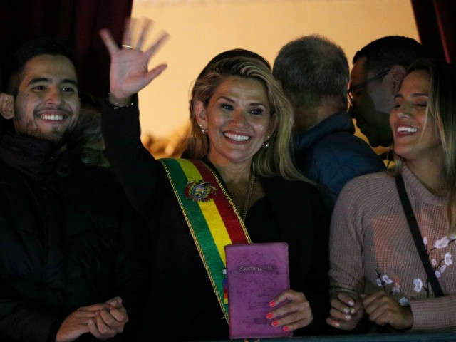 Bolivia's second Senate Vice President and opposition politician Jeanine Anez, center, wearing the Presidential sash, addresses the crowd from the balcony of the Quemado palace after she declared herself interim president of the country, in La Paz, Bolivia, Tuesday, Nov. 12, 2019. (AP Photo/Juan Karita)