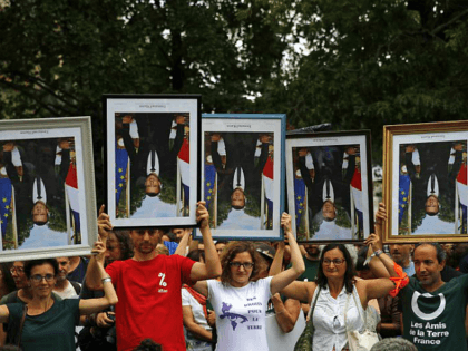 FILE - In this Aug.25, 2019 file photo, demonstrators hold up upside down portraits of French President Emmanuel Macron during a protest in Bayonne, France. One by one, environmental activists around France have been taking portraits of President Emmanuel Macron down from scattered town halls this year. The portrait-removers, have …