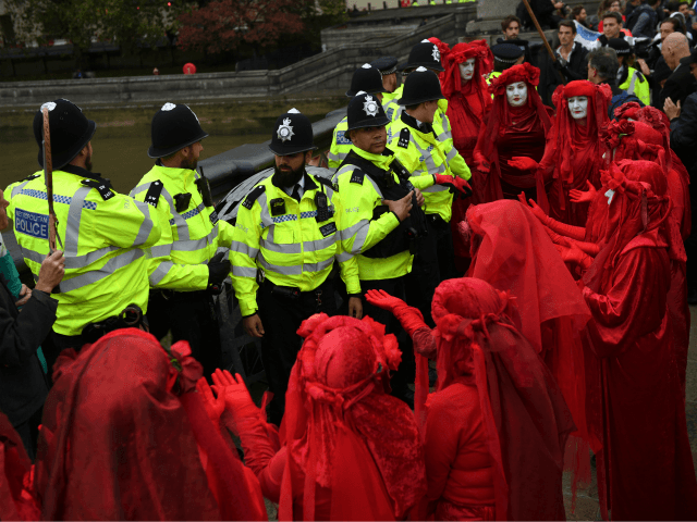 LONDON, ENGLAND - OCTOBER 07: The Red Brigade of The Invisible Circus gesture to police in Westminster on October 7, 2019 in London, England. Climate change activists are gathering to block access to various government departments as they start a two week protest in central London (Photo by Chris J …
