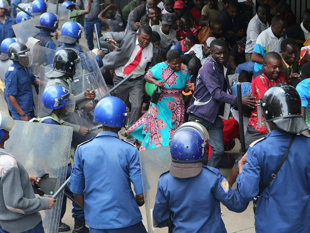 Police surround opposition party supporters who had gathered to hear a speech by the country's top opposition leader in Harare, Wednesday, Nov. 20, 2019. Zimbabwean police with riot gear fired tear gas and struck people who had gathered at the opposition party headquarters to hear a speech by the main …