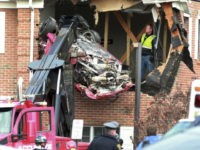 Porsche is removed form the second story of a building after the convertible went airborne and crashed into the second floor of a New Jersey commercial building early Sunday, killing both of the car's occupants, in Toms River, N.J. (Ed Murray/NJ Advance Media via AP)