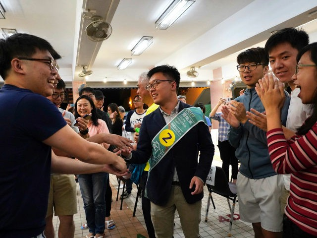 Pro-democracy candidate James Yu, center, celebrates with supporters after winning his seat in district council elections in Hong Kong, early Monday, Nov. 25, 2019. Vote counting was underway in Hong Kong on Sunday after a massive turnout in district council elections seen as a barometer of public support for pro-democracy …