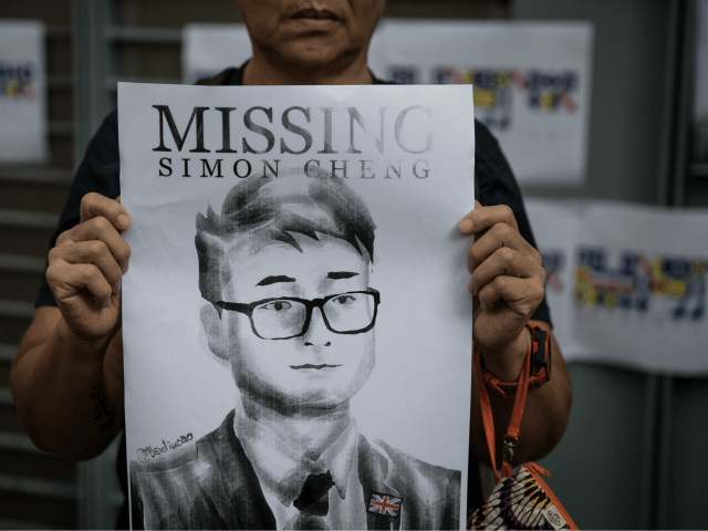 HONG KONG, CHINA - AUGUST 21: A woman holds a poster showing a portrait of British consulate worker Simon Cheung, who was detained 14 days ago by Chinese officials during a gathering to petition the British government to assist in the his release, outside the British Consulate on August 21, …