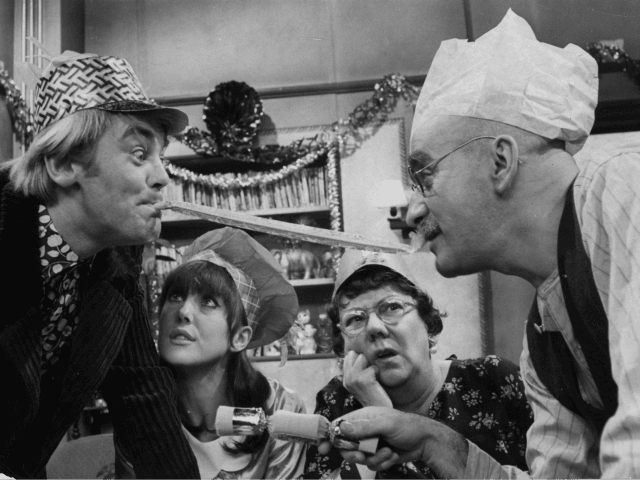 30th November 1966: Alf Garnett, played by Warren Mitchell, and his son-in-law Mike, played by Anthony Booth, arguing over the Christmas dinner table in a scene from the popular BBC comedy series 'Till Death Do Us Part'. From left to right, Anthony Booth, Una Stubbs, Dandy Nichols and Warren Mitchell. …