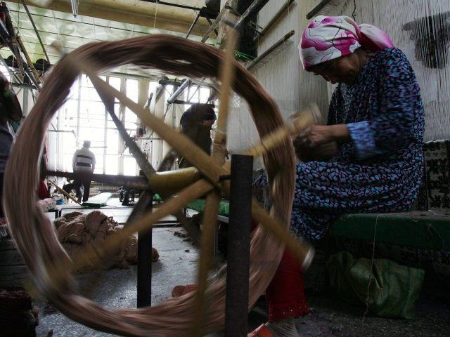 "Uigur women weave carpets in the Hetian Carpet Factory on September 4, 2007 in Hetian of Xinjiang Uygur Autonomous Region, China. Hetian, nicknamed in China as ""Carpet Country,"" has a 3,000 year history of carpet weaving. Xinjiang has been noted in ancient times along the old silk road as a …"