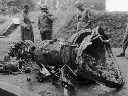 Soldiers examine the wreckage of a German V-2 rocket bomb which fell in Belgium and was not destroyed. Signal corps caption states that engine which is believed to be fed by a mixture of liquid air with either oxygen or alcohol is at left. This is first picture of a …