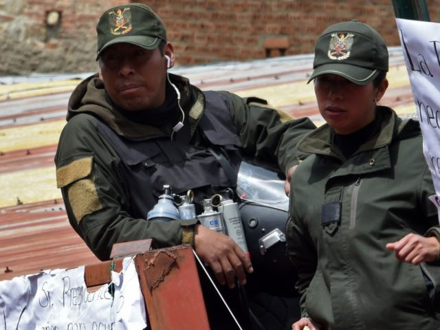Policemen with a sign against ex-President Evo Morales gather at the police's Special Tactical Operations Unit headquarters in La Paz on November 11, 2019. - Bolivia's Evo Morales announced his resignation on Sunday, caving in following three weeks of sometimes-violent protests over his disputed re-election after the army and police …