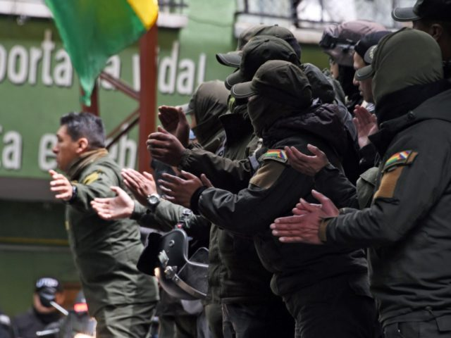 Policemen applaud during a meeting at the police's Special Tactical Operations Unit headquarters in La Paz on November 11, 2019. - Bolivia's Evo Morales announced his resignation on Sunday, caving in following three weeks of sometimes-violent protests over his disputed re-election after the army and police withdrew their backing. (Photo …