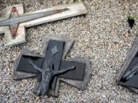 "A photo taken on April 15, 2015 shows a broken crucifix on the ground after tombstones were found vandalized at the Saint-Roch cemetery in Castres, southern France. French President Francois Hollande condemned ""in the strongest terms"" the vandalism of ""dozens of Christian tombs"" at the Saint-Roch cemetery, qualifying the acts …"
