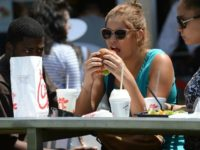 A woman eats lunch on the patio of the Chick-fil-A in Hollywood, California, August 1, 2012. Thousands of Americans turned out Wednesday to feast on fried chicken in a politically-charged show of support for a family owned fast-food chain which opposes same-sex marriage. Long lines and traffic jams were reported …