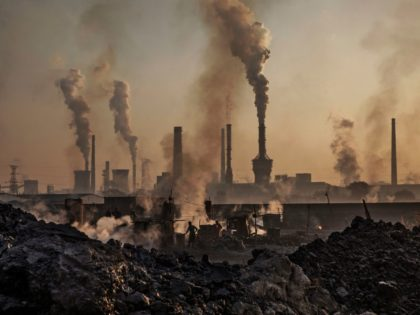 INNER MONGOLIA, CHINA - NOVEMBER 04: Smoke billows from a large steel plant as a Chinese labourer works at an unauthorized steel factory, foreground, on November 4, 2016 in Inner Mongolia, China. To meet China's targets to slash emissions of carbon dioxide, authorities are pushing to shut down privately owned …