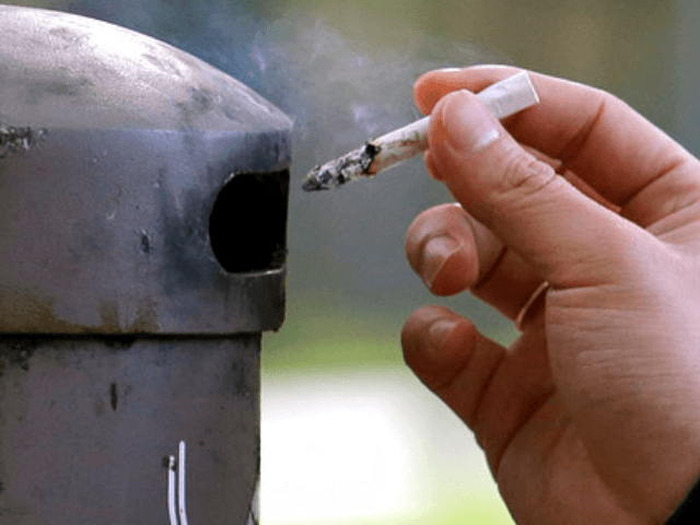 In this Oct. 27, 2015, file photo, a University of Washington student discards a cigarette into a container at a designated smoking locations on the campus in Seattle. Seventeen public health schools in the U.S. and Canada have pledged to refuse research money from a new anti-smoking group funded by …