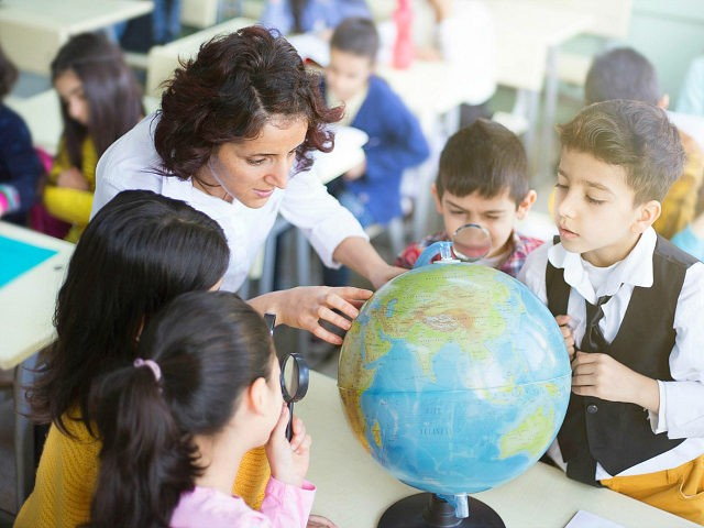 female teacher and students looking the globe with a magnifying glass in the classroom