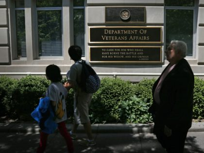 Pedestrians walk in front of the Department of Veterans Affairs building in Washington, Friday, June 21, 2013. The number of military suicides is nearly double that of a decade ago when the U.S. was just a year into the Afghan war and hadn't yet invaded Iraq. While the pace is …