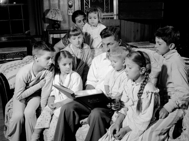 circa 1956: A whole family gathered in the evening for readings of their favourite Bible stories. (Photo by Sherman/Three Lions/Getty Images)