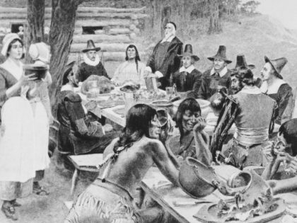 A depiction of early settlers of the Plymouth Colony sharing a harvest Thanksgiving meal with members of the local Wampanoag tribe at the Plymouth Plantation, Plymouth, Massachusetts, 1621. (Photo by Frederic Lewis/Archive Photos/Getty Images)