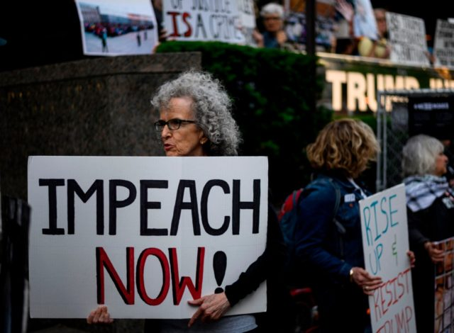 """A demonstrator with a sign reading """"Impeach now"""" takes part in Trumps Birthday Protest in front of the Trump International Tower, June 14, 2019 in New York City. - A group of activists protested against his immigration policy. (Photo by Johannes EISELE / AFP) (Photo credit should read JOHANNES EISELE/AFP …"""