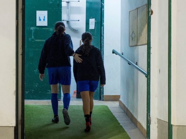 Two girls walk into de locker room after attending a training session at the Anorga KKE football school in the Spanish Basque city of San Sebastian on February 18, 2019. (Photo by ANDER GILLENEA / AFP) (Photo credit should read ANDER GILLENEA/AFP via Getty Images)