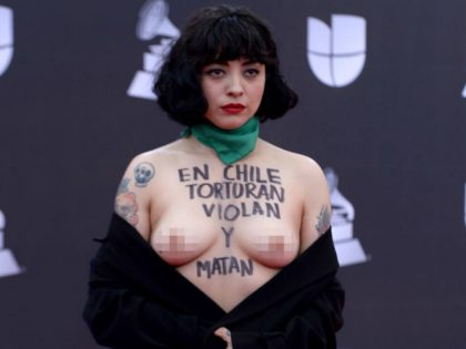 "TOPSHOT - EDITORS NOTE: Graphic content / Chilean singer Mon Laferte, exposes her breast with writings reading ""In Chile they torture, rape and kill"", as she arrives at the 20th Annual Latin Grammy Awards in Las Vegas, Nevada, on November 14, 2019. (Photo by Bridget BENNETT / AFP) (Photo by …"