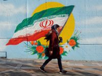 An Iranian woman walks past a mural painting of the Islamic republic's national flag in central Tehran on November 21, 2019. (Photo by - / AFP) (Photo by -/afp/AFP via Getty Images)