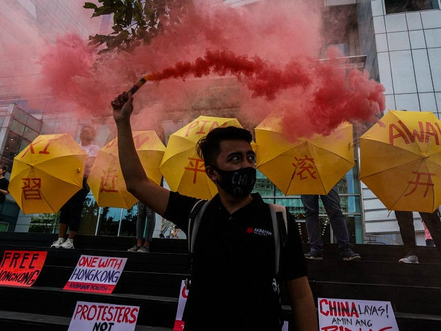 Activists holding umbrellas in support of pro-democracy protesters in Hong Kong stand in front of the Chinese consulate in the financial district of Manila on November 27, 2019. - The group expressed their solidarity with the pro-democracy protesters of Hong Kong, condemning the increased violence by police against students and …