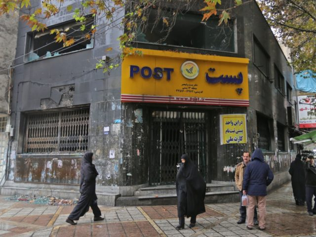 """Iranians gather outside a post office branch that was damaged during demonstrations against petrol price hikes, on November 20, 2019 in Shahriar, west of Tehran. - Three security personnel have been killed by """"rioters"""" in Iran, the latest deaths in protests that showed no sign of subsiding today despite a …"""