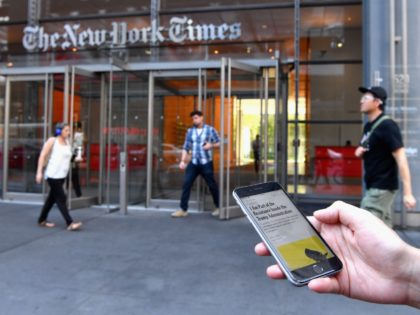 "A smartphone displaying a New York Times opinion piece titled ""I Am Part of the Resistance Inside the Trump Administration"" is held up in this illustration in front of the New York Times building on September 6, 2018 in New York. - A furious Donald Trump called September 5, 2018 …"