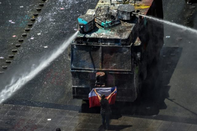 A demonstrator stands in front of police water cannon in Santiago, Chile, which has been rocked by protests