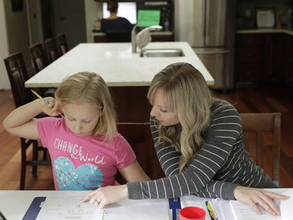 In this Oct. 9, 2019 photo, Donya Grant, right, works on a homeschool lesson with her daughter Mabry, 8, in their home in Monroe, Wash. The family joined a lawsuit against the Monroe School District and others, alleging that the district failed to adequately respond to PCBs, or polychlorinated biphenyls, …