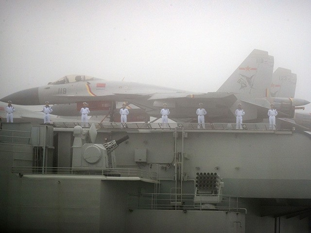 FILE - In this April 23, 2019, file photo, sailors stand near fighter jets on the deck of the Chinese People's Liberation Army (PLA) Navy aircraft carrier Liaoning as it participates in a naval parade in the sea near Qingdao in eastern China's Shandong province. China says its first entirely …