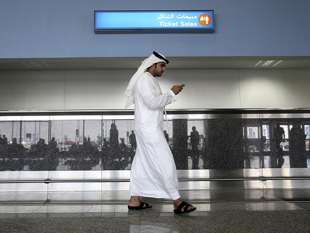 FILE - In this Oct. 27, 2013 file photo, a worker looks at his mobile phone at the newly opened Al Maktoum International Airport in Dubai, United Arab Emirates. According to a New York Times report, ToTok, a chat app that quickly became popular in the United Arab Emirates for …