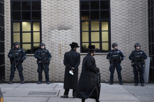 FILE - In this Dec. 11, 2019 file photo, Orthodox Jewish men pass New York City police guarding a Brooklyn synagogue prior to a funeral for Mosche Deutsch in New York. Deutsch, a rabbinical student from Brooklyn, was killed in the shooting inside a Jersey City, N.J. market. New York …